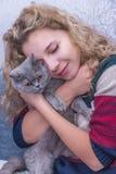 拥抱一只灰色猫的女孩 库存照片