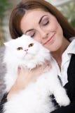 拥抱一只白色波斯猫的女孩 免版税库存照片