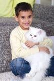 拥抱一只白色波斯猫的男孩 图库摄影