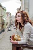 拥抱一套圆的发光设备的年轻美丽的女孩,当走老市的街道利沃夫州时 免版税库存照片
