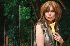 拥抱一朵花的女孩在森林里由镜子 免版税库存照片