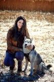拥抱一条多壳的狗的美丽的少妇 势均力敌 免版税图库摄影