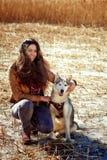 拥抱一条多壳的狗的美丽的少妇 势均力敌 库存图片