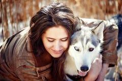 拥抱一条多壳的狗的美丽的少妇 势均力敌 库存照片