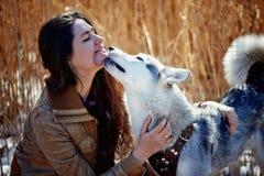 拥抱一条多壳的狗的美丽的少妇 势均力敌 免版税库存照片