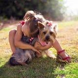 拥抱一条小狗的逗人喜爱的女孩 免版税图库摄影