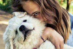 拥抱一条比利牛斯山脉的山狗的一只逗人喜爱的小狗的愉快的青少年的女孩拿着它在她的手上在夏日户外 免版税库存照片