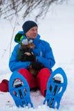 拥抱一条滑稽的小狗的雪靴的愉快的旅客 免版税库存图片