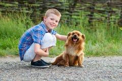 拥抱一条红色蓬松狗的格子花呢上衣的男孩 最好的朋友 室外 免版税库存图片