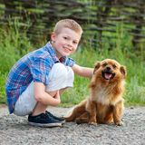 拥抱一条红色蓬松狗的格子花呢上衣的男孩 最好的朋友 Ou 库存照片