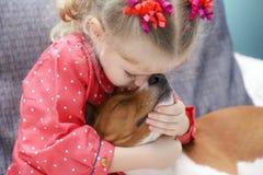 拥抱一条红色basenji狗的小白肤金发的卷曲女孩 库存图片