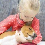 拥抱一条红色basenji狗的小白肤金发的卷曲女孩 免版税图库摄影