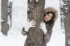 拥抱一棵树的妇女在冬天森林里 爱恋的本质 图库摄影