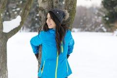 拥抱一棵树的妇女在冬天森林里 爱恋的本质 免版税图库摄影