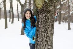 拥抱一棵树的妇女在冬天森林里 爱恋的本质 免版税库存照片