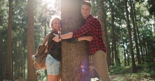 拥抱一棵树的微笑的夫妇在森林 库存照片