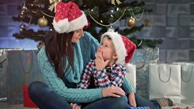 拥抱一起坐和谈话的微笑的年轻母亲和小逗人喜爱的孩子在圣诞树附近 股票录像