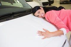 拥抱一辆白色汽车的微笑的妇女 库存照片
