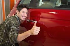 拥抱一辆红色汽车的微笑的人,当给赞许时 免版税图库摄影