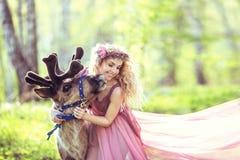 拥抱一头驯鹿的美丽的女孩在森林里 免版税图库摄影