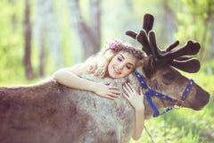 拥抱一头驯鹿的美丽的女孩在森林里 图库摄影