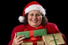 拥抱三件被包裹的礼物的高兴年长妇女 免版税库存照片