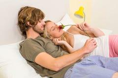 拥抱与女朋友的逗人喜爱的夫妇嗅到玫瑰 库存照片