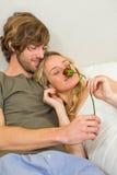 拥抱与女朋友的逗人喜爱的夫妇嗅到玫瑰 库存图片