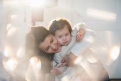 拥抱与她的母亲的小女孩在一个好冬天穿衣,婴孩,生活方式,童年,喜悦,家庭价值观,生活方式 免版税图库摄影