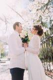 年轻拥抱与春天花束的新娘和新郎在篱芭附近开花 免版税库存图片