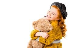 拥抱与闭合的眼睛的愉快的红色头发孩子玩具熊 库存图片
