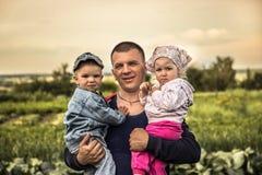 拥抱两个逗人喜爱的小孩子儿子和女儿的愉快的微笑的父亲在象征愉快的育儿的乡下 库存图片