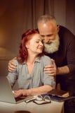 拥抱中部年迈的夫妇uisng膝上型计算机 免版税库存照片