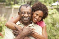 拥抱人前辈的成人女儿 免版税库存图片