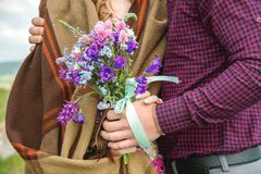 拥抱人和他的女朋友的夫妇的特写镜头手的有花束的 免版税库存照片