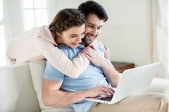 拥抱人的微笑的妇女,当使用膝上型计算机时 库存图片
