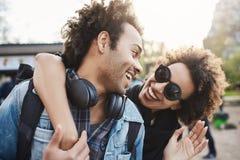 拥抱从后面的快乐的深色皮肤的妇女特写镜头画象男朋友,当走在公园和谈话,微笑时 免版税库存图片