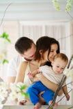 拥抱他们小儿子和亲吻的父母 免版税库存照片