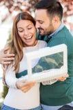 拥抱他的妻子或女朋友的愉快的年轻人 妇女在打开礼物盒以后微笑着 免版税库存图片