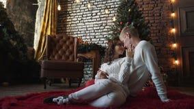 拥抱他的妻子的一个年轻英俊的丈夫,如果一个新年树、礼物和蜜桔的前面在他们附近 丢弃系列 股票视频