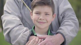 拥抱他的孙子的正面微笑的小男孩和无法认出的成熟人画象在公园 r 影视素材