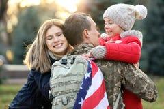 拥抱他的家庭的美国战士 图库摄影