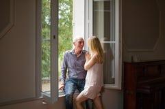 拥抱他的年轻白肤金发的妻子的牛仔裤和衬衣的老人站立在窗口附近在他们的家在夏时 免版税库存照片