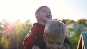 拥抱他的弟弟的男孩和在他的肩膀拿着他 儿童` s笑声和喜悦 日落 股票录像