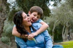 拥抱他的母亲的孩子微笑在秋天下午 免版税库存照片