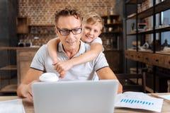 拥抱他的父亲的愉快的男孩,当研究膝上型计算机时的他 免版税库存图片