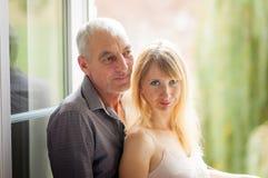 拥抱他的Windows背景的老人画象年轻妻子户内 免版税库存图片