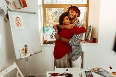 拥抱他美丽的女朋友的爱的英俊的有胡子的人 库存图片