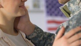 拥抱伪装制服的,战士归乡的微笑的年轻妻子丈夫 影视素材