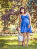 拥抱使用的怀孕的母亲和女儿画象外面 免版税库存图片